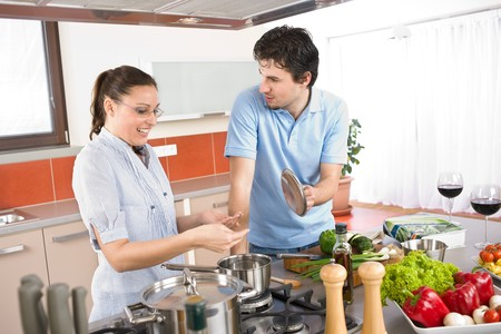 Young happy couple cooking in modern kitchen with vegetables photo