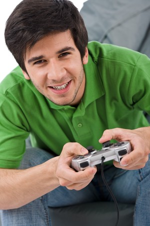 Young happy man playing video game with control pad on white background photo