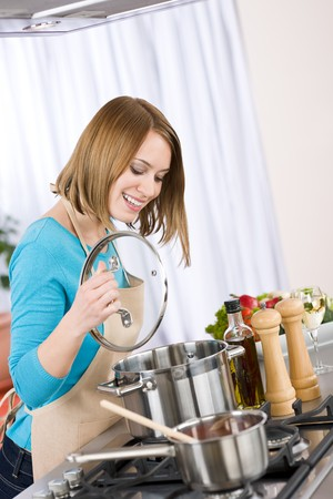 Cooking - Happy woman by stove in kitchen with pots and pans Stock Photo - 6914645