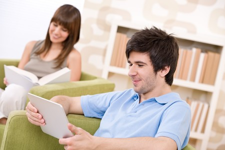 Students - young man with touch screen computer sitting on armchair in loung with woman photo