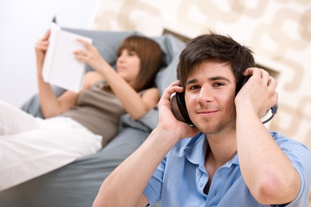 Student - Teenager man relaxing with headphones, woman reading book relaxing on bean bag Stock Photo - 6914747