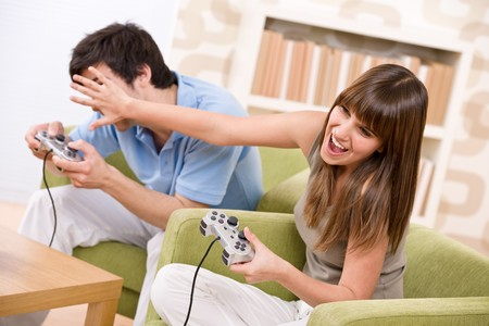 Student - happy teenagers playing video game with control pad in living room photo