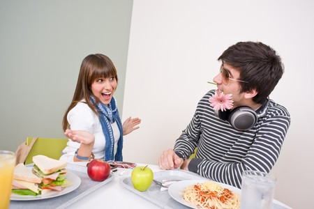 Student cafeteria - teenage couple having fun during lunch break photo