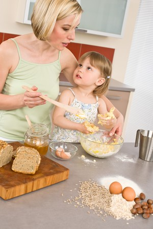 Baking - Woman with child preparing dough with healthy ingredients photo