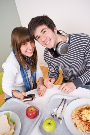 Student cafeteria - Happy teenagers having lunch break photo