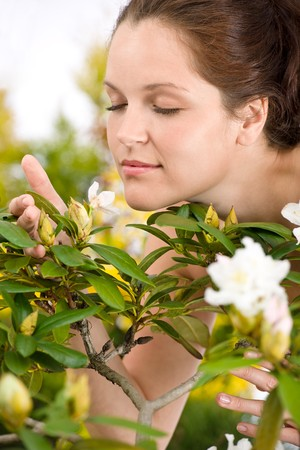 Gardening - Woman smelling blossom flower on white background photo
