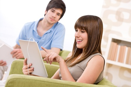 Student - teenage woman with touch screen tablet computer on armchair in lounge with man photo