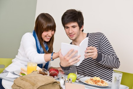 Student cafeteria - Teenagers having lunch break, holding book photo