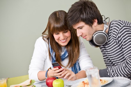 Student cafeteria - teenage couple with mobile phone during lunch break photo
