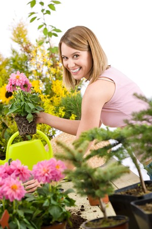 smiling woman in a greenhouse: Gardening - Happy woman holding flower pot with blossoming flower on white background