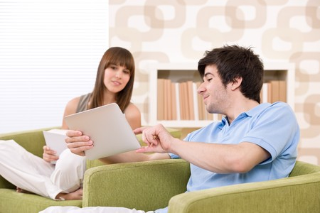 Student - young man with touch screen tablet computer sitting on armchair in lounge with woman photo