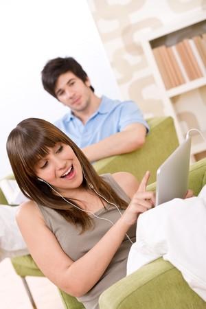 �cran tactile: �tudiant - femme teenage avec tactile �cran tablet PC sur un fauteuil dans loung avec homme