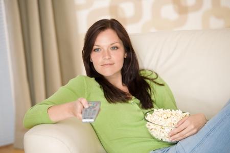 ver television: Mujer viendo la televisi�n con palomitas de ma�z en la sala de estar, manteniendo el control remoto