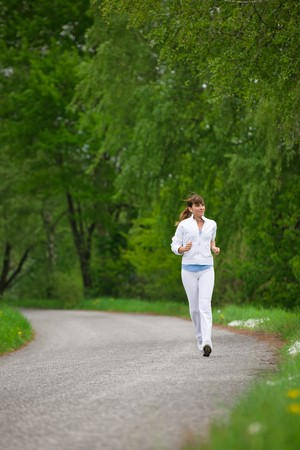Jogging - sportive woman running on road in nature, listen to music with earbuds Stock Photo - 7021888