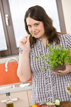 Cook - plus size woman with herb and vegetable in modern kitchen photo