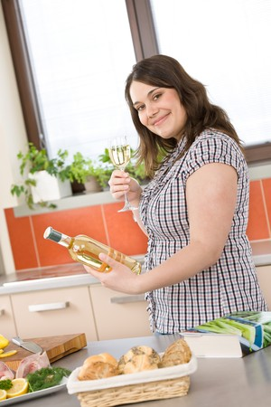 Cook - plus size woman prepare fish with white wine in modern kitchen photo