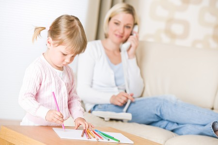 Little girl draw with color pencil in lounge, mother with phone calling photo