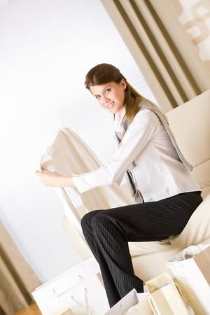 uitpakken: Jonge zaken vrouw zittend op de bank met luxe boodschappen tas, pak nieuwe kleren