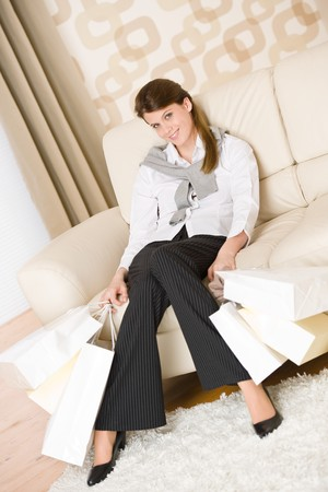 Smiling business woman with shopping bag sitting on sofa in lounge Stock Photo - 7061414