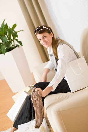 Young businesswoman with shopping bag on sofa, plant in background Stock Photo - 7061416