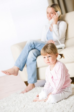 Mother and child in living room watch television, mother on phone in background on sofa photo