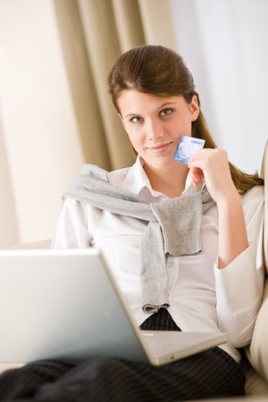 Home shopping - woman with credit card and laptop in lounge Stock Photo
