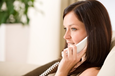 On the phone home - woman calling in living room Stock Photo - 7093670