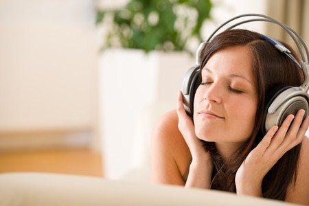 Woman with headphones listen to music in lounge, plant in background