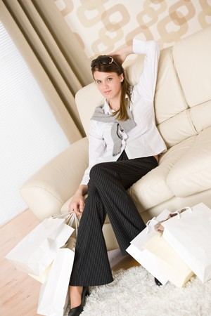 Smiling business woman with shopping bag sitting on sofa in lounge Stock Photo - 7121916