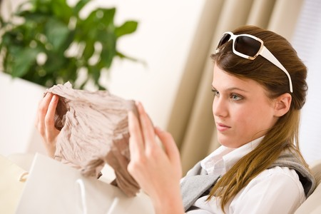 Young businesswoman unpacking shopping bag on sofa, plant in background Stock Photo - 7113518