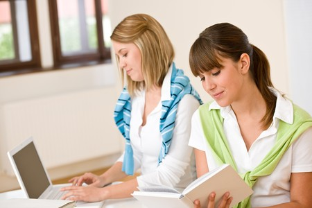 revision book: Student at home - two woman with book and laptop study together