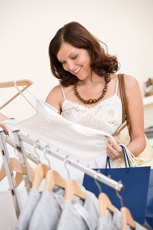 Fashion shopping - Happy young woman in shop choose clothes holding shopping bag photo