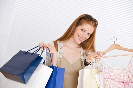 Fashion shopping - Happy woman with bag and sale dress photo