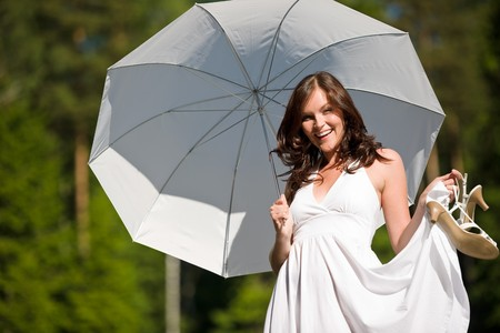 sunglight: Happy romantic woman with parasol in sunglight wearing white dress, holding shoes