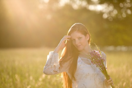 long red hair woman: Long red hair woman in romantic sunset meadow holding bunch of flowers