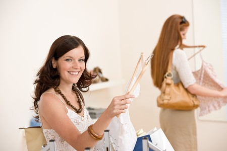 Fashion shopping -  Two happy young woman choose clothes in shop photo