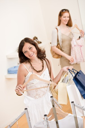 Fashion shopping -  Two happy young woman choose clothes in shop holding shopping bag Stock Photo - 7169563