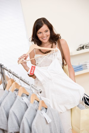 Fashion shopping - Happy woman choose sale clothes, holding shopping bag photo