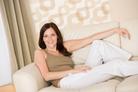 woman on couch: Smiling woman relax sitting on sofa in lounge Stock Photo