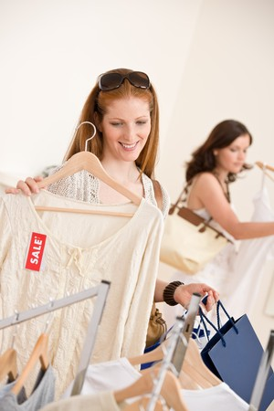 Fashion shopping -  Two happy young woman choose clothes in shop Stock Photo - 7169701