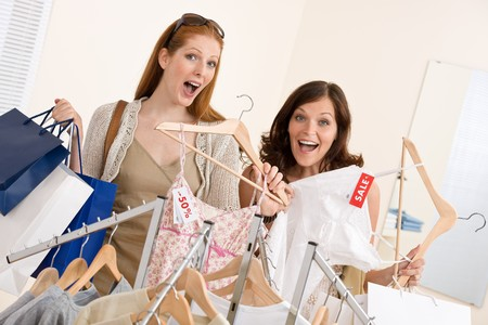clothing rack: Fashion shopping -  Two happy young woman choose clothes in shop holding shopping bag Stock Photo