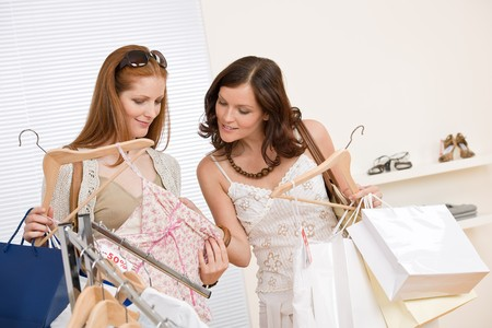 Fashion shopping -  Two happy young woman choose clothes in shop holding shopping bag photo