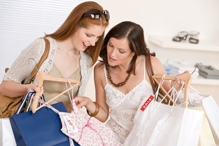 Fashion shopping -  Two happy young woman choose clothes in shop holding shopping bag Stock Photo - 7169759
