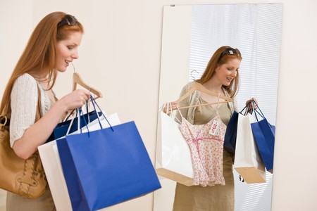 Fashion shopping - Happy woman choose sale clothes, holding shopping bag in mirror photo