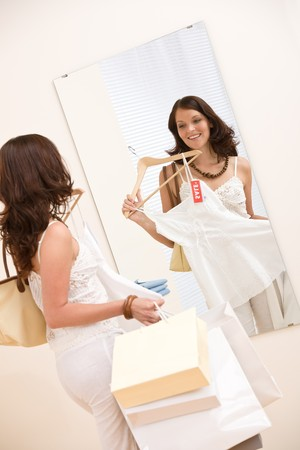 Fashion shopping - Happy woman choose sale clothes, holding shopping bag in mirror