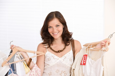 Fashion shopping - Happy woman choose sale clothes, holding shopping bag Stock Photo - 7169739
