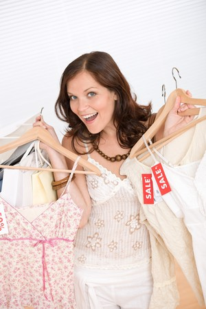 Fashion shopping - Happy woman choose sale clothes, holding shopping bag Stock Photo - 7169741