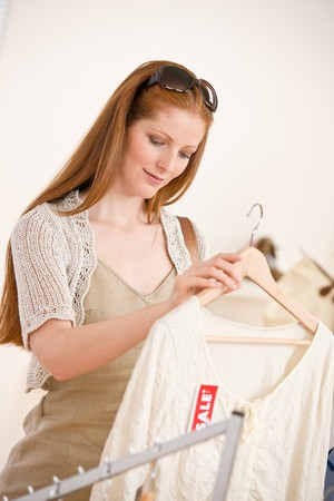 Fashion shopping - red hair woman choose sale clothes in shop photo
