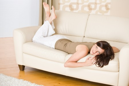 Young woman relax lying down on sofa in lounge photo