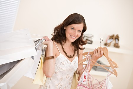 Fashion shopping - Happy woman choose sale clothes, holding shopping bag Stock Photo - 7173386